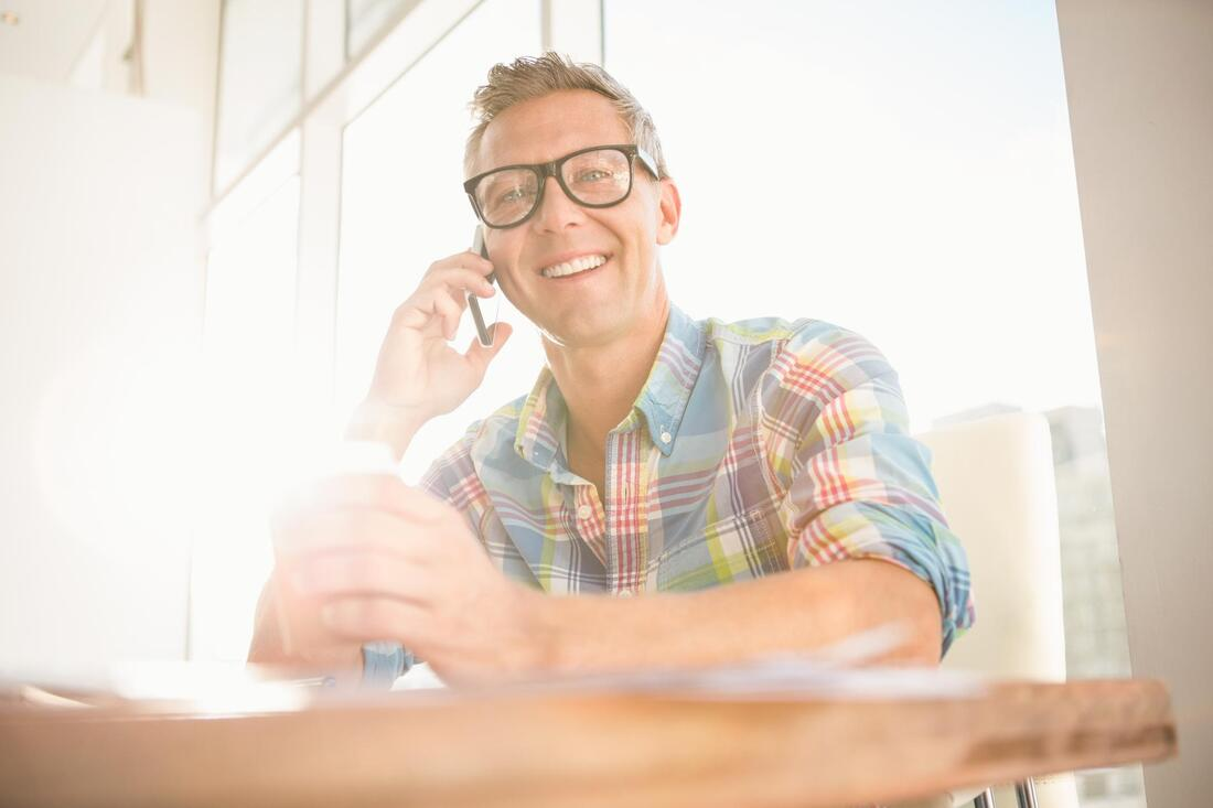 man smiling taking phone call